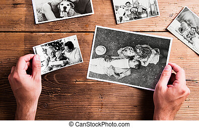 Hands holding various pictures of senior couple. Studio...