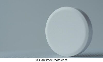 white tablets turning on a white background