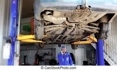auto mechanic discussing with customer on mobile phone under lifted automobile