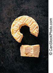 Top view on portion cut from whole golden camembert cheese -...