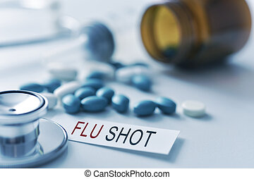 stethoscope, pills and text flu shot - closeup of the desk...