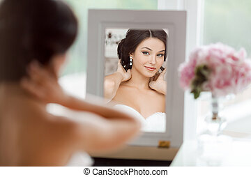Portrait of the young beautiful bride looks at herself in...