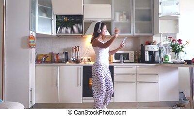 Joyful young beautiful woman is dancing in kitchen wearing...