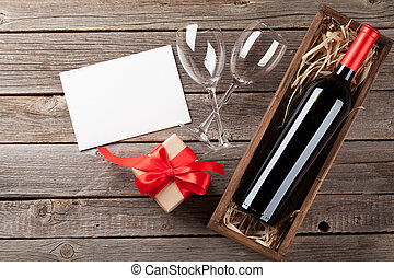 Valentines day greeting card. Wine and gift box on wooden...