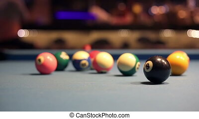 Playing Eight-ball pool billiards in a bar