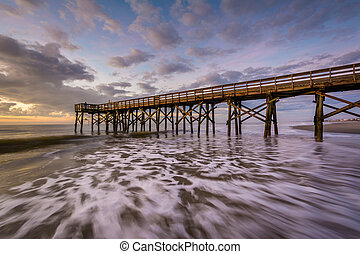 Waves in the Atlantic Ocean and the pier at sunrise, in Isle...