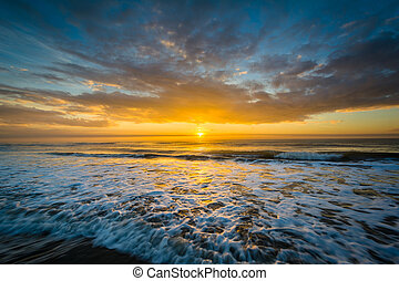 Waves in the Atlantic Ocean and sunrise, in Isle of Palms,...