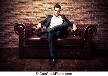 Chesterfield sofa - Imposing well dressed man in a luxurious...