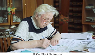 Elderly woman writing in journal, notebook, grandmother, 4k...