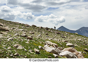 Woman Hiking On Ridge - distant woman hiking up a ridgeline...