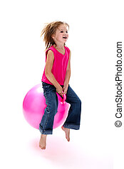Girl bouncing - Young laughing girl bouncing on a pink space...