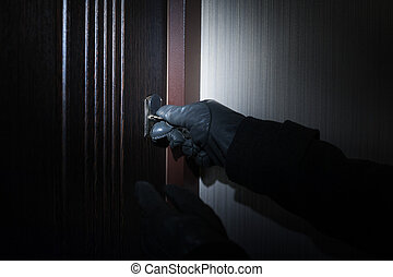 man wearing gloves opens the door at night.