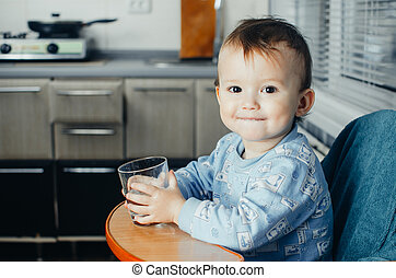 child drinks water from a glass