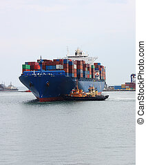 cargo ships - tugboats pulling  container vessel