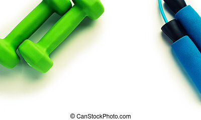 Green dumbbells and skipping rope for fitness on white background