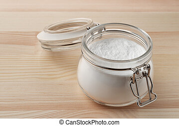 Open glass jar of baking soda on wooden background