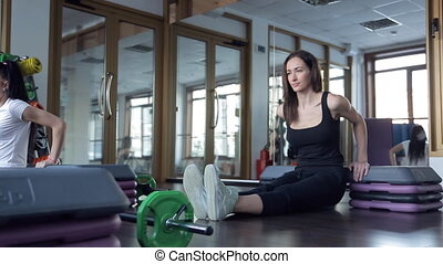 Fitness instructor demonstrates exercises rocking press in gym.