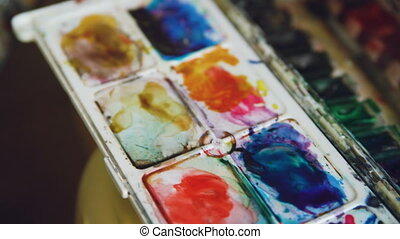 Young woman artist draw pictrure with watercolor paints and brush on easel canvas closeup hand
