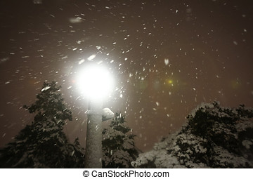 Street lamp during snowfall - A low angle view of an...