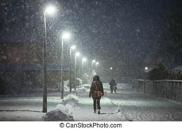 Woman walking in snowy street - A rear view of a woman...