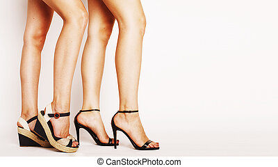 two pair of woman legs in hight heels shoes isolated on...