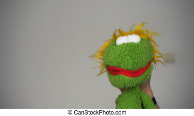 Funny green puppet laughting in camera