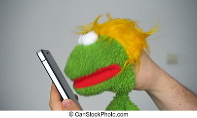 Funny green puppet browsing in smartphone at white...