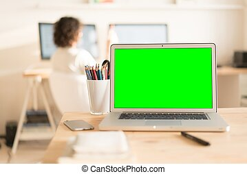 Green screen laptop computer and glass with pencils on table...