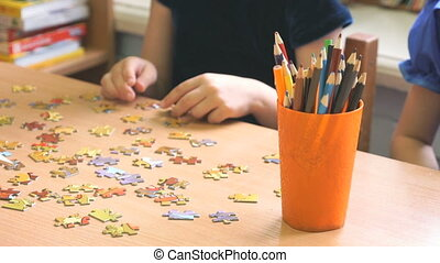 Little girls play the game collecting puzzles - Two little...