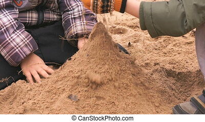 Two little boys playing with sand in sandbox - Two little...