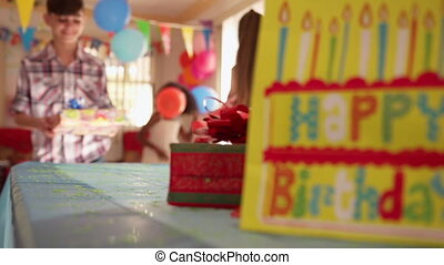 Child Putting Present On Table During Birthday Party At Home...