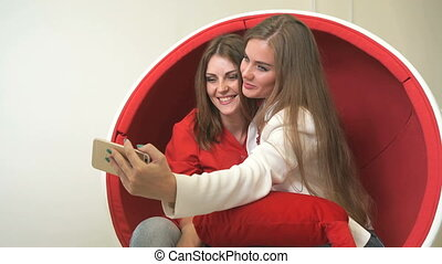 Two girls sitting in red chair, making selfies - Attractive...