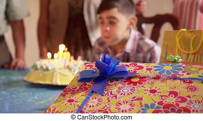 Party With Happy Hispanic Child Blowing Candles On Cake -...
