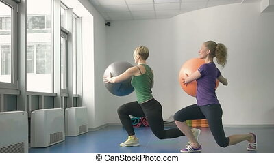 sporty women doing gymnastic exercises or exercising in fitness class