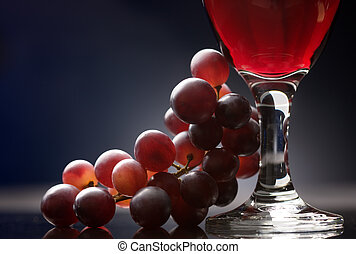 Red wine with grapes - Close-up of a glass of red wine with...