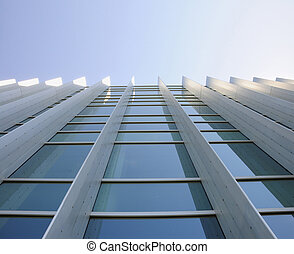 Exterior windows of a commercial office building looking up from the ground with blue sky refected in windows