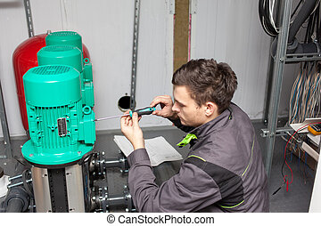 Young engineer at the plant - Young electrician, repairs...