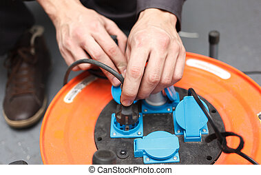 Hands of young electrician.
