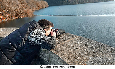 Photographer with camera on a lake. - Photographer with...