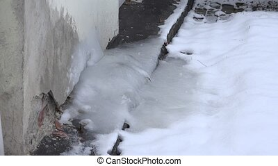 Ice pile frozen under recuperator heat pump system on house wall in winter.