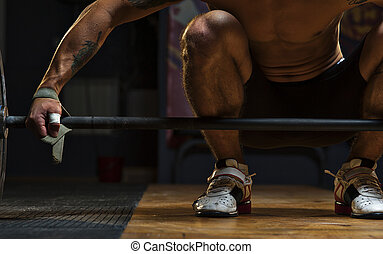 Male athlete preparing for exercise with barbell - Cropped...