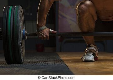 Young muscular man lifting barbell in gym, closeup - Cropped...