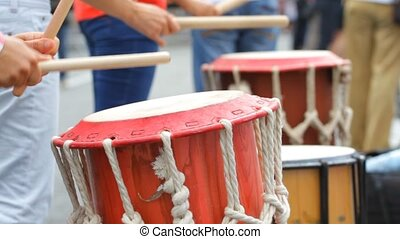 Street musician playing on the wooden drums.