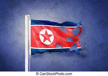 Torn flag of North Korea flying against grunge background.