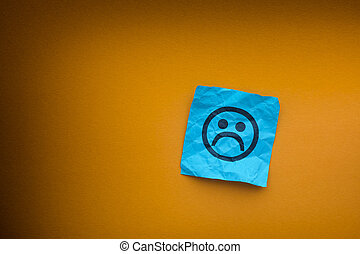 Blue paper note with sad face on a yellow paper background....