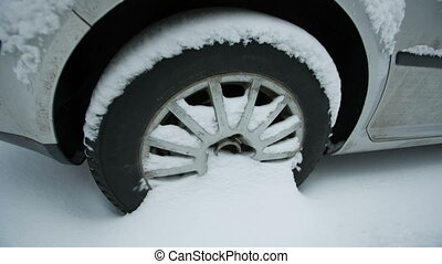 Wheel of a car in snow - A car wheel covered with snow