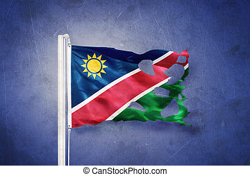 Torn flag of Namibia flying against grunge background.