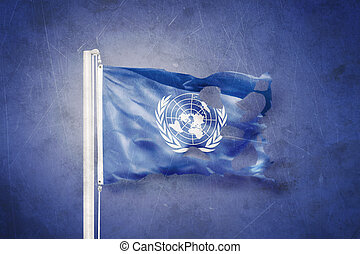 Torn flag of the United Nations waving against grunge...