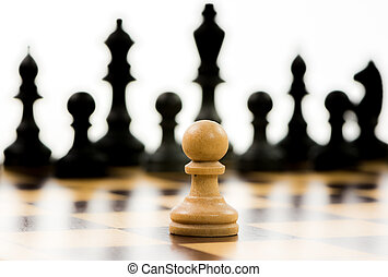 White pawn against a superiority of black chess pieces on a...