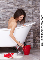 Bathing woman relaxing in bath smiling relaxing and drinking...